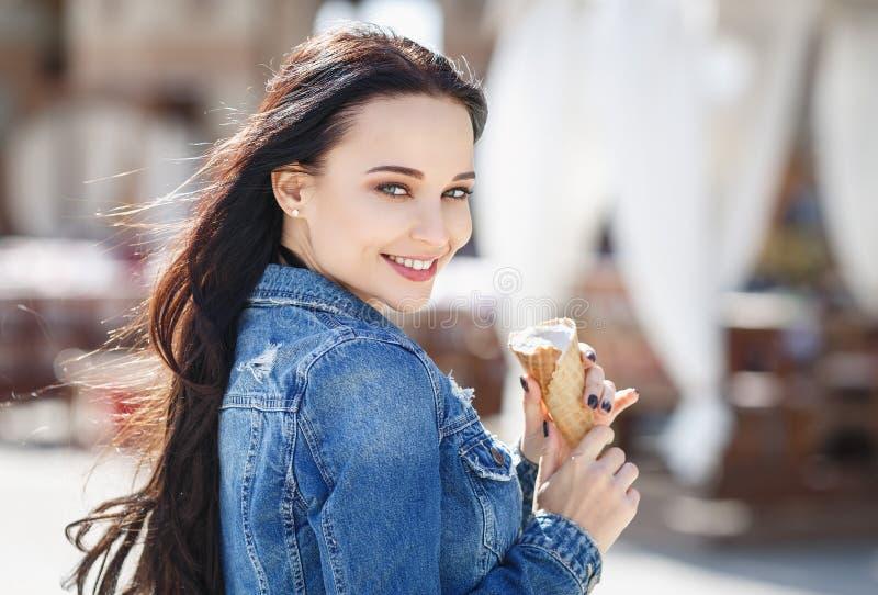 Muchacha hermosa en una chaqueta que come el helado fotografía de archivo libre de regalías