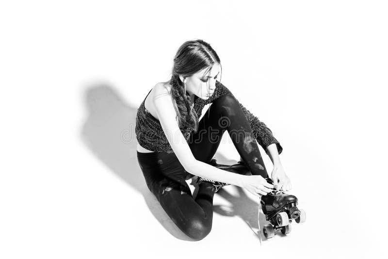 Muchacha hermosa en una sentada negra con los rodillos y el cordón foto de archivo libre de regalías