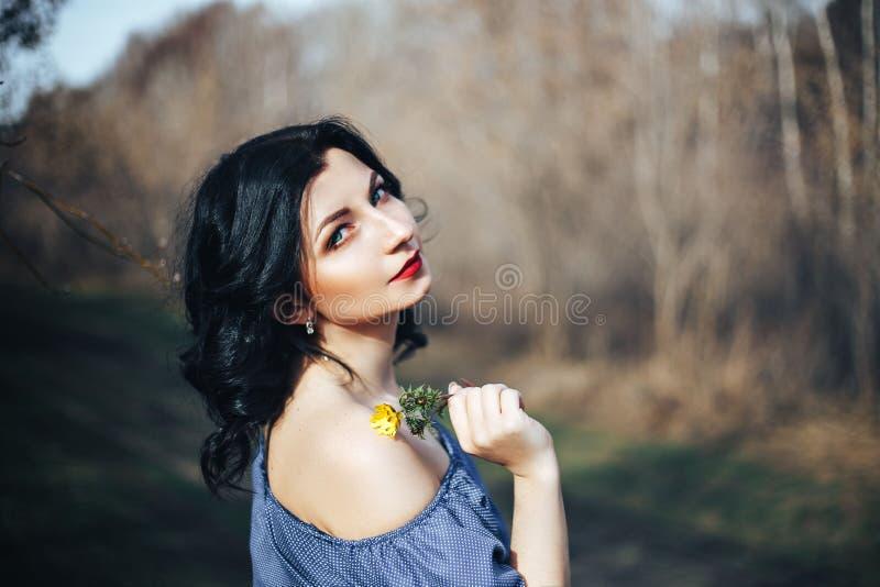 Muchacha hermosa en vestido azul y flor amarilla fotos de archivo libres de regalías