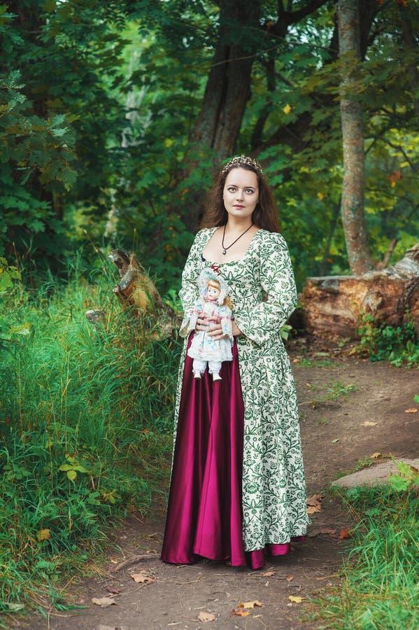 Muchacha hermosa en vestido medieval largo con la muñeca del vintage fotos de archivo
