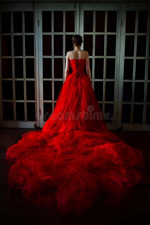 Muchacha hermosa en vestido rojo largo y en corona real imagenes de archivo