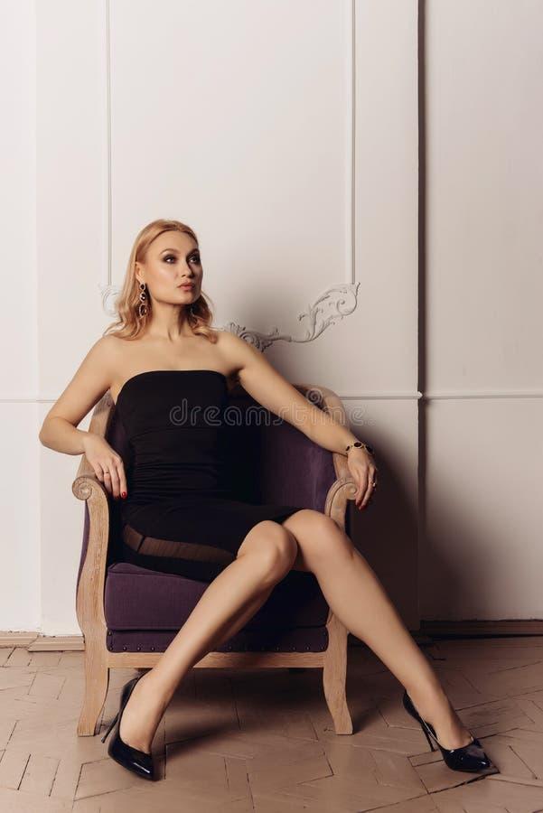 Muchacha hermosa en vestido y zapatos negros en la silla antigua t retro imágenes de archivo libres de regalías