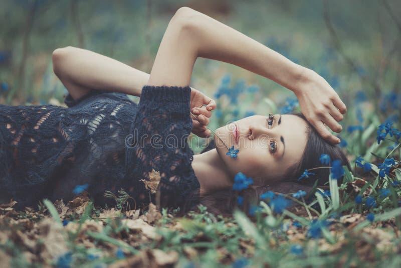 Muchacha hermosa entre los snowdrops en el bosque imagen de archivo