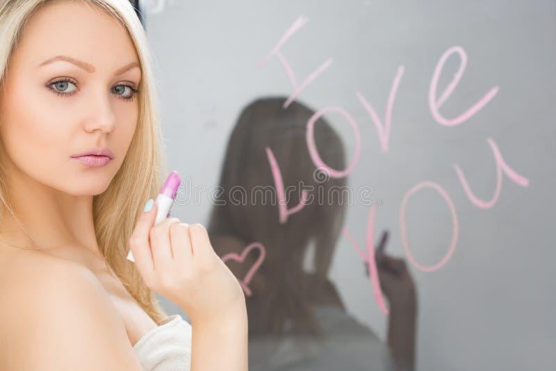 Muchacha hermosa escrita en un espejo en el lápiz labial, I foto de archivo