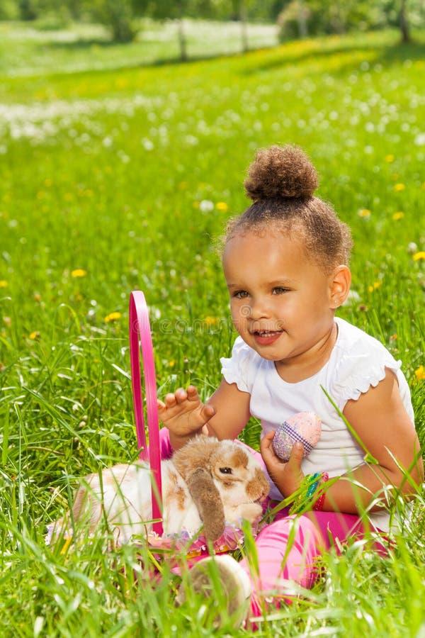 Muchacha hermosa feliz con el huevo y el conejo del este imagen de archivo
