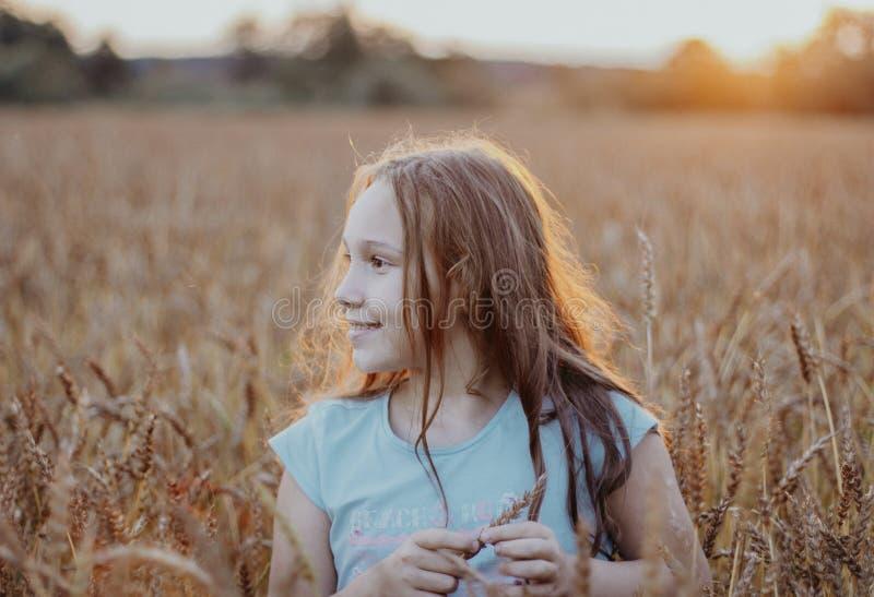 Muchacha hermosa feliz de los tweenes con el pelo largo en campo de trigo en el tiempo de la puesta del sol foto de archivo