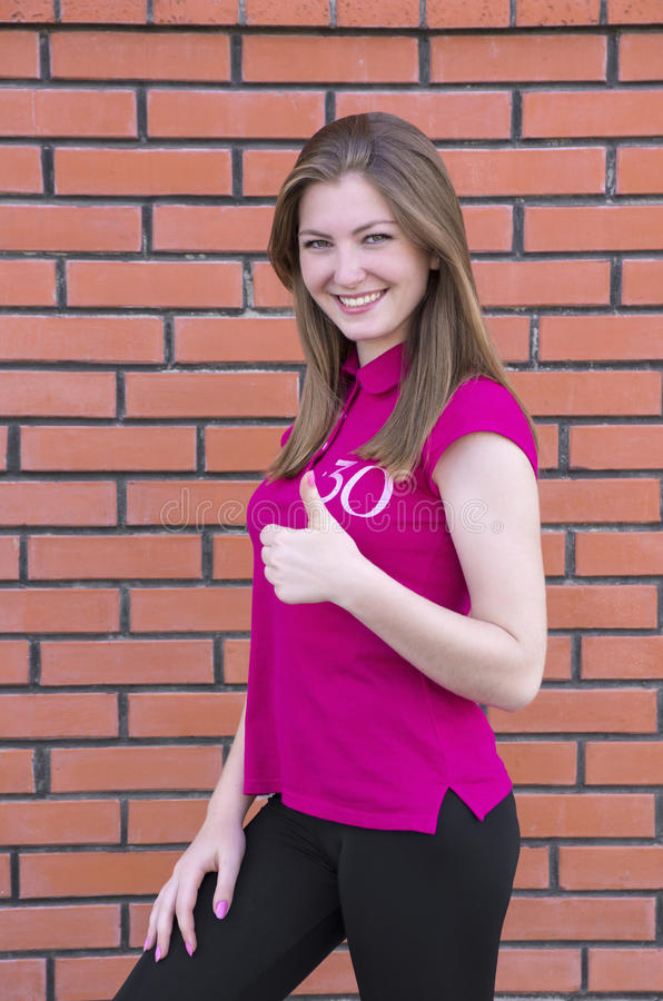 Muchacha hermosa feliz que muestra el pulgar encima del símbolo fotografía de archivo libre de regalías
