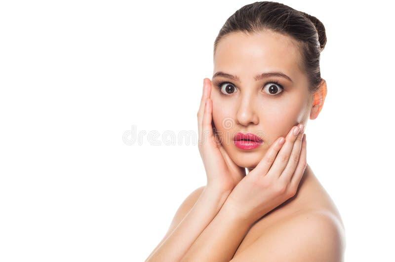 Muchacha hermosa feliz que sostiene sus mejillas con una risa que mira al lado Expresiones faciales expresivas Cosmetología y BAL imagen de archivo