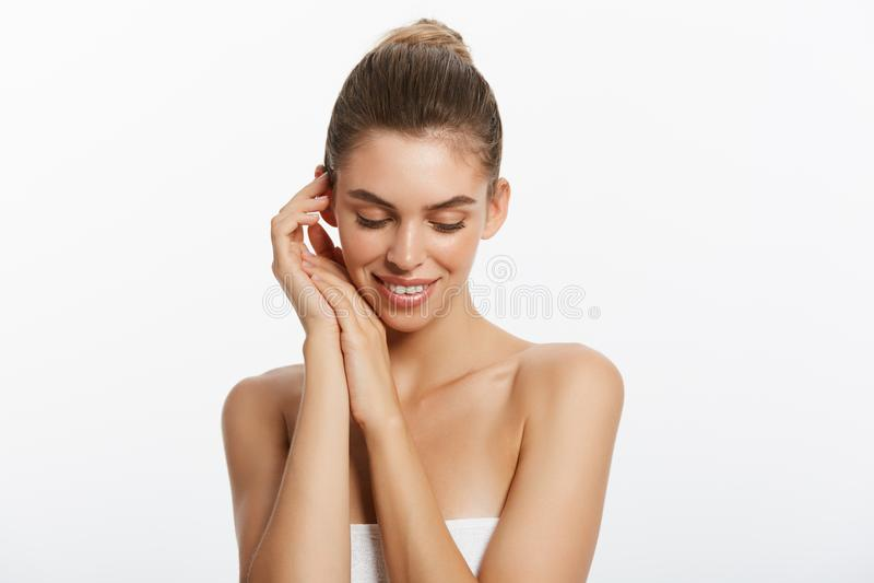 Muchacha hermosa feliz que sostiene sus mejillas con una risa que mira al lado Expresiones faciales expresivas Cosmetología y fotografía de archivo libre de regalías