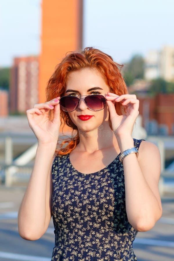 Muchacha hermosa joven con aspecto hermoso Mujer pelirroja con una cara bonita en la puesta del sol El encantar, retrato sonrient foto de archivo