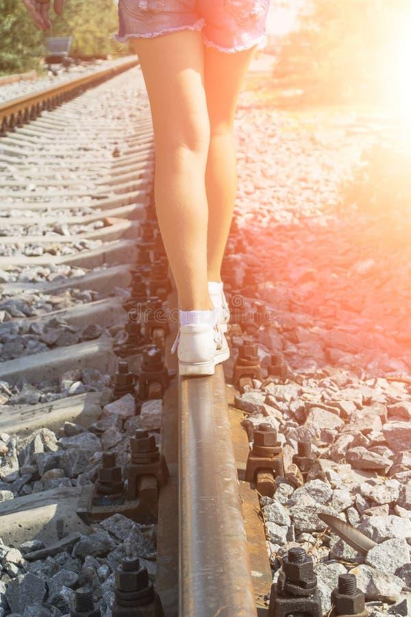 Muchacha hermosa joven con caminar rosado del pelo, equilibrando en los carriles fotografía de archivo