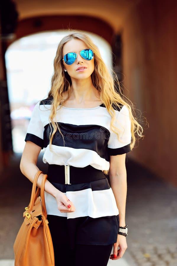 Muchacha hermosa joven con el bolso y las gafas de sol fotografía de archivo libre de regalías
