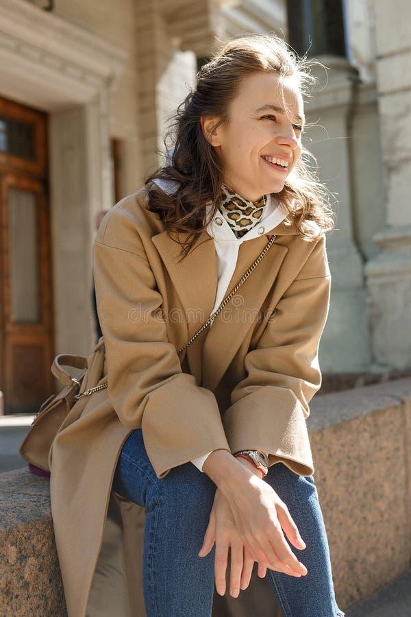 Muchacha hermosa joven con el pelo largo en capa beige en un día soleado que se sienta en un encintado y una sonrisa Retrato del  fotos de archivo