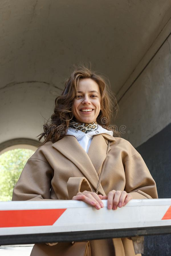 Muchacha hermosa joven con el pelo largo en capa beige en una situación del día soleado cerca de la sonrisa del arco Retrato del  imágenes de archivo libres de regalías