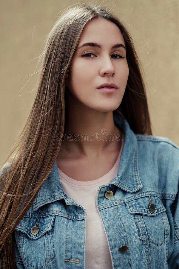 Muchacha hermosa joven con el pelo largo en una chaqueta de la camiseta y del dril de algodón en el fondo del muro de cemento del imagen de archivo