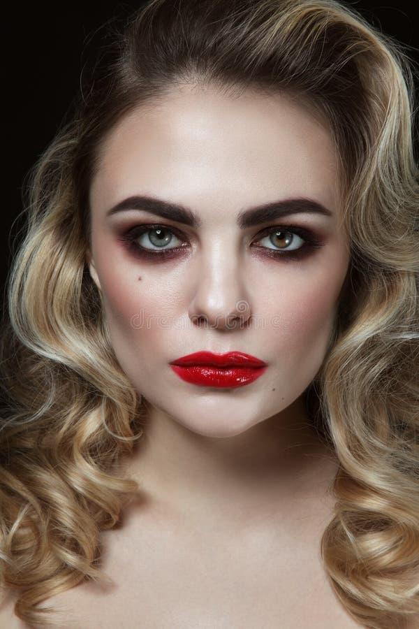 Muchacha hermosa joven con el pelo rizado rubio y el lápiz labial rojo fotos de archivo libres de regalías