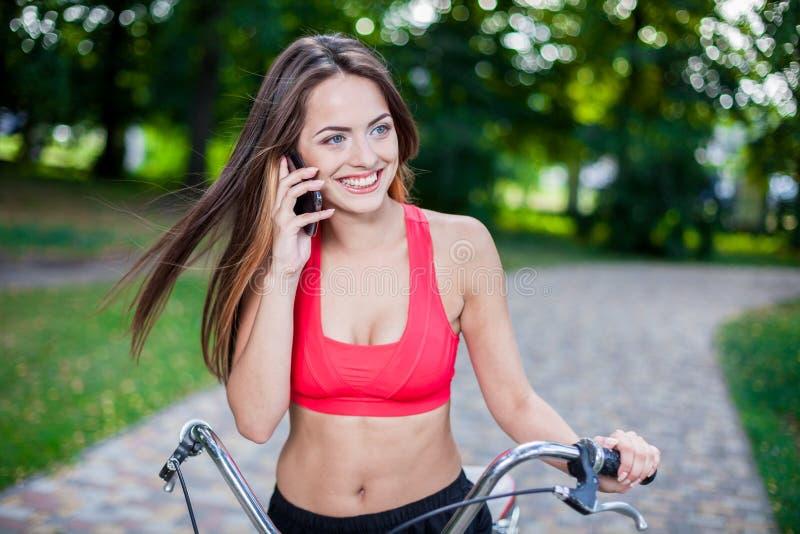 Muchacha hermosa joven con la bici foto de archivo