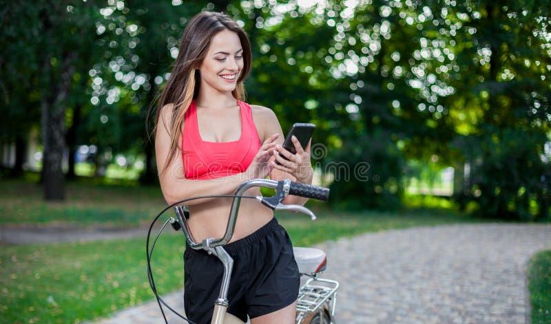 Muchacha hermosa joven con la bici imagenes de archivo