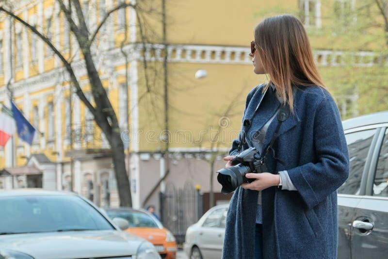 Muchacha hermosa joven con la c?mara en la ciudad de la primavera, turista de la muchacha que toma las fotograf?as en la calle de imagen de archivo