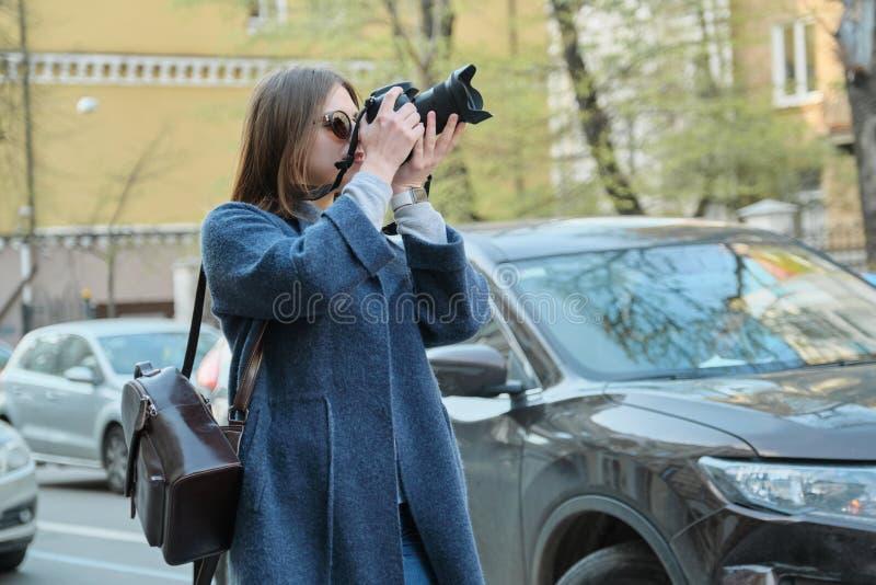 Muchacha hermosa joven con la c?mara en la ciudad de la primavera, turista de la muchacha que toma las fotograf?as en la calle de foto de archivo libre de regalías