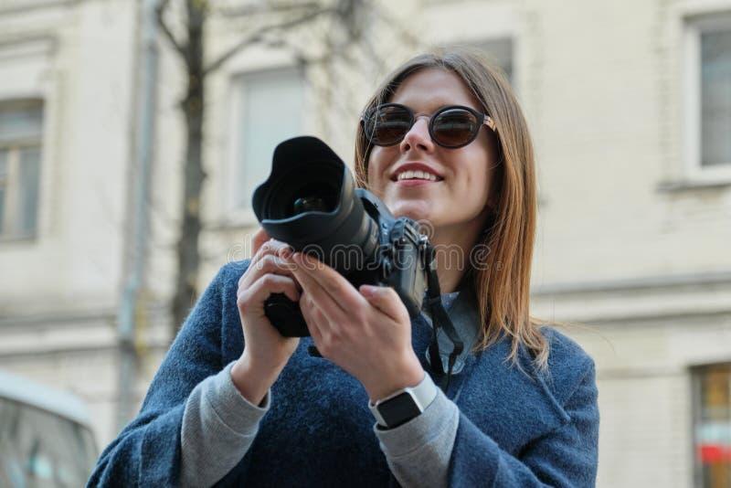 Muchacha hermosa joven con la c?mara en la ciudad de la primavera, turista de la muchacha que toma las fotograf?as en la calle de fotos de archivo libres de regalías