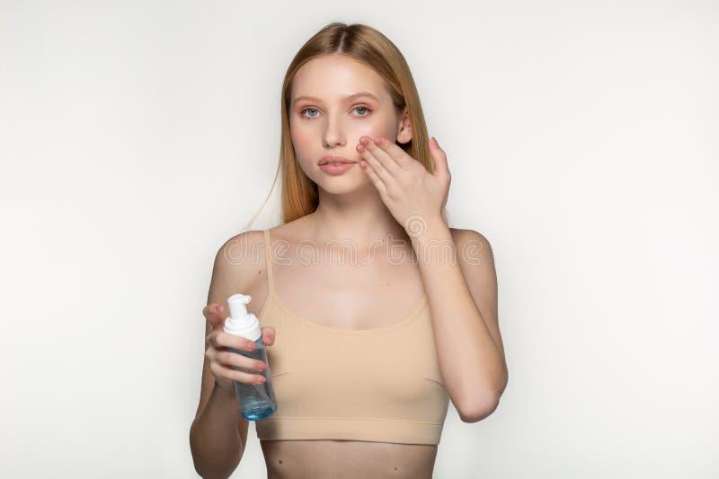 Muchacha hermosa joven con la piel perfecta que aplica la crema cosm?tica en la cara aislada en fondo gris en el estudio foto de archivo