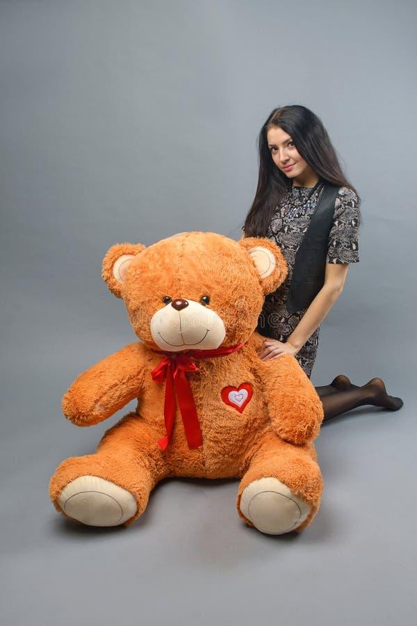 Muchacha hermosa joven con la sonrisa feliz de peluche del juguete suave grande del oso y jugar en fondo gris foto de archivo