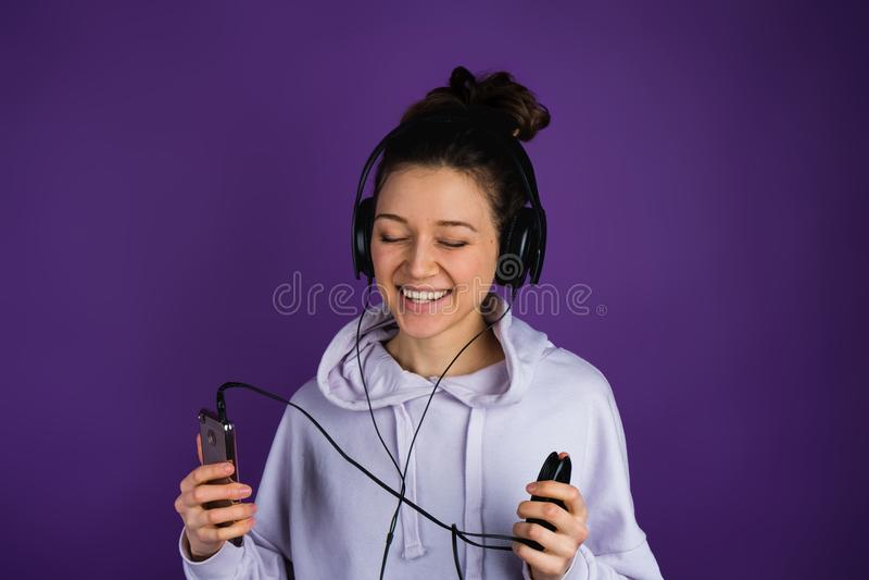 Muchacha hermosa joven con los dientes blancos que escucha la música en los auriculares que llevan del teléfono en una camiseta e fotos de archivo libres de regalías