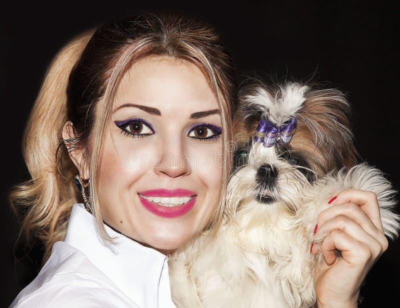 Muchacha hermosa joven con un lápiz labial del rosa de Shih Tzu del perro recogido fotos de archivo