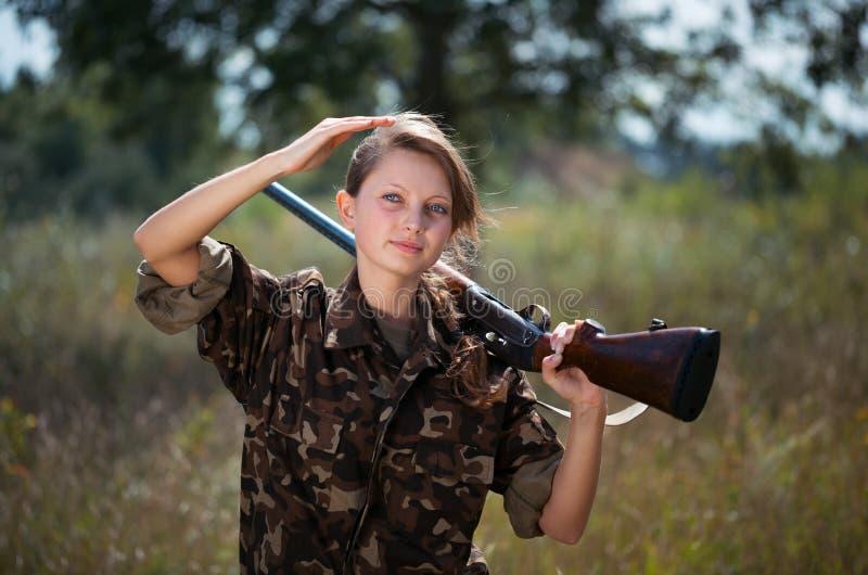 Muchacha hermosa joven con una escopeta en un al aire libre foto de archivo libre de regalías