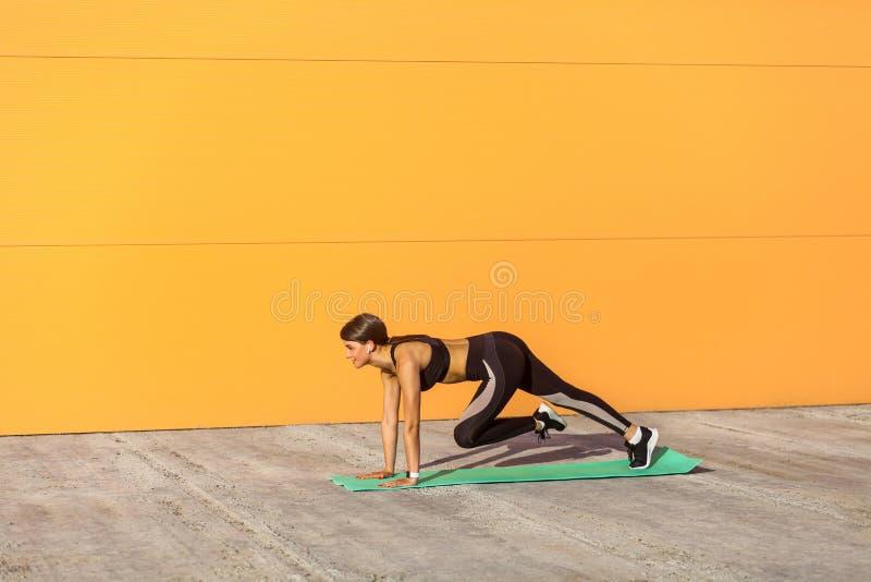 Muchacha hermosa joven de la aptitud en sportwear negro en la calle del verano que hace ejercicio del ABS para entonar los múscul foto de archivo