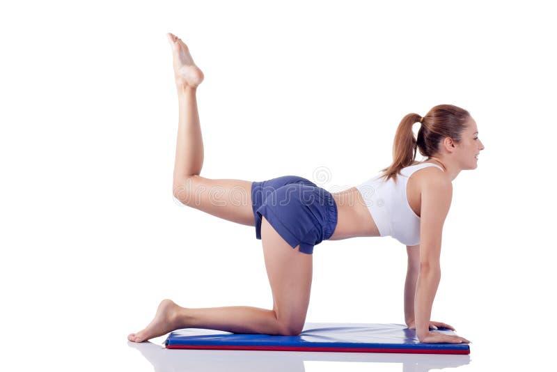 Muchacha hermosa joven de la aptitud que hace el ejercicio aislado en blanco imagen de archivo
