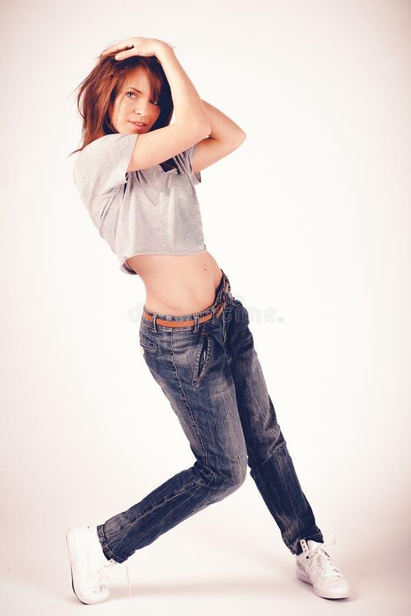 Muchacha hermosa joven de la mujer en el baile rojo de los pantalones y de la camisa de tela escocesa foto de archivo libre de regalías