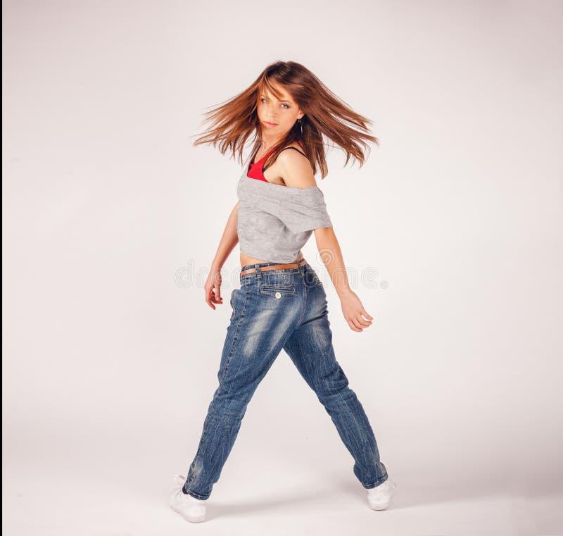 Muchacha hermosa joven de la mujer en el baile rojo de los pantalones y de la camisa de tela escocesa imágenes de archivo libres de regalías
