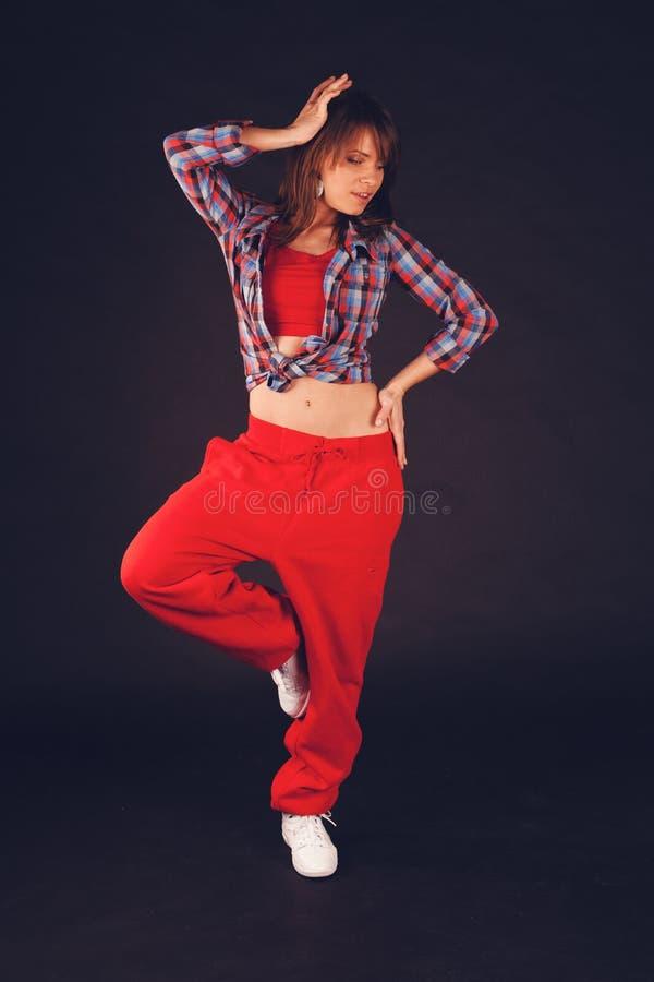 Muchacha hermosa joven de la mujer en el baile rojo de los pantalones y de la camisa de tela escocesa fotos de archivo
