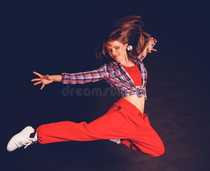 Muchacha hermosa joven de la mujer en el baile rojo de los pantalones y de la camisa de tela escocesa fotografía de archivo libre de regalías