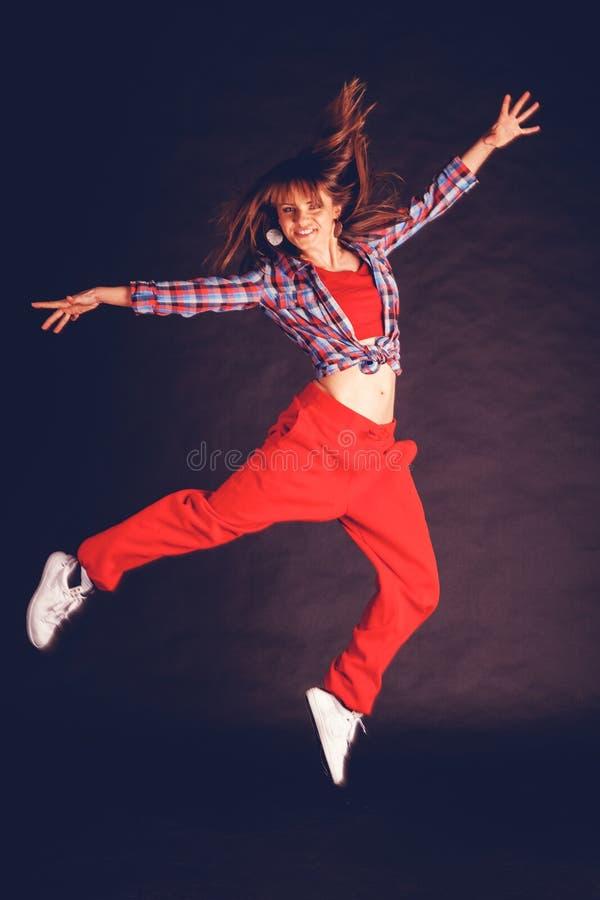 Muchacha hermosa joven de la mujer en el baile rojo de los pantalones y de la camisa de tela escocesa fotos de archivo libres de regalías