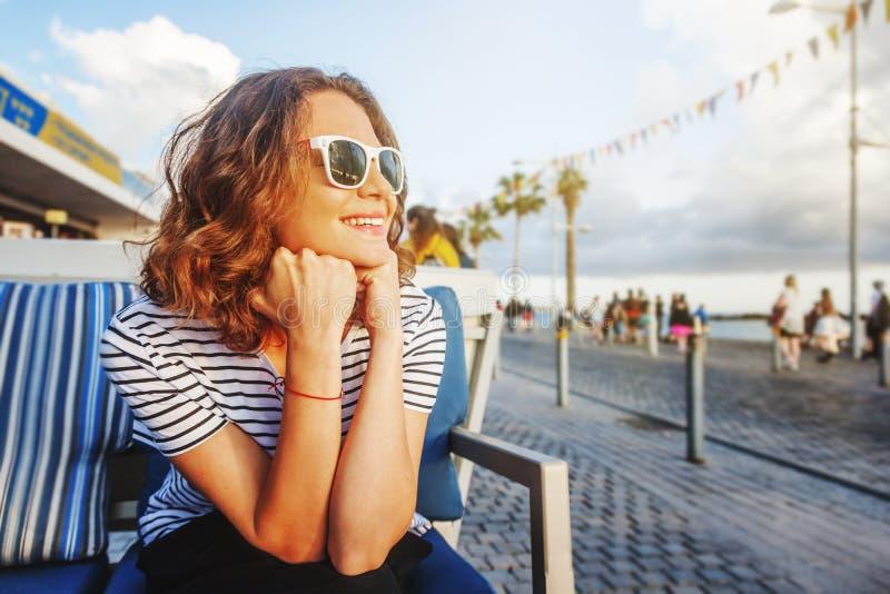 Muchacha hermosa joven de la mujer en una camiseta rayada que se sienta en un str imágenes de archivo libres de regalías