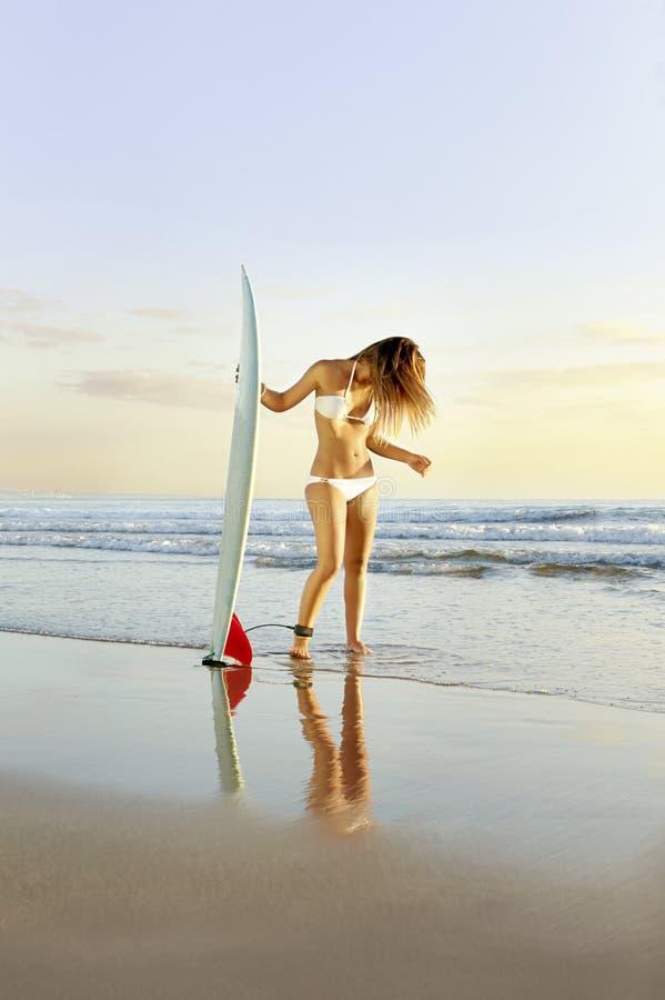 Muchacha hermosa joven de la persona que practica surf que se coloca en la playa con la tabla hawaiana fotos de archivo