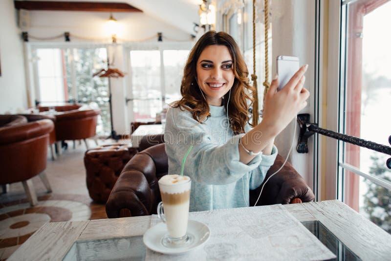 Muchacha hermosa joven en café que habla en la charla video imagen de archivo
