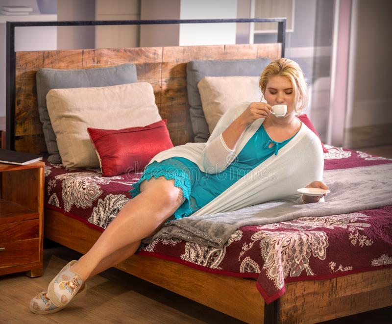 Muchacha hermosa joven en el café de consumición de la cama imagen de archivo libre de regalías