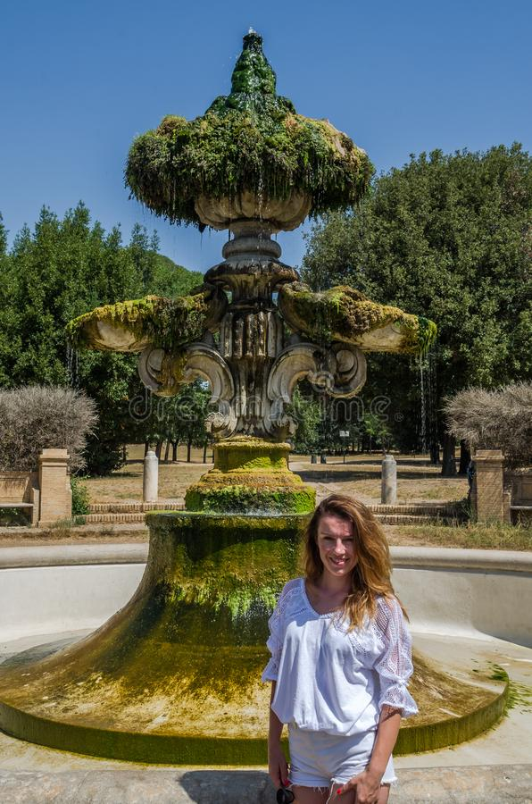 Muchacha hermosa joven en el fondo de una fuente antigua mientras que camina en el parque en el chalet Doria Pamphili en Roma, It imagen de archivo libre de regalías