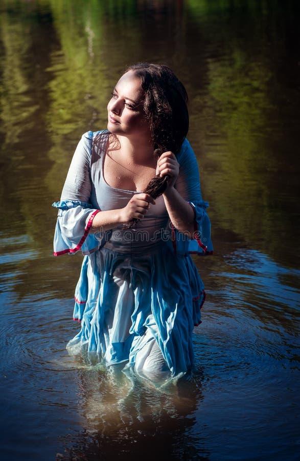 Muchacha hermosa joven en el vestido azul largo que se coloca en el río fotos de archivo libres de regalías