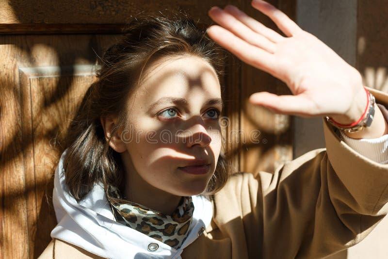 Muchacha hermosa joven en la capa beige que presenta en una sombra en un día soleado que lleva a cabo su mano delante de ella imagen de archivo libre de regalías