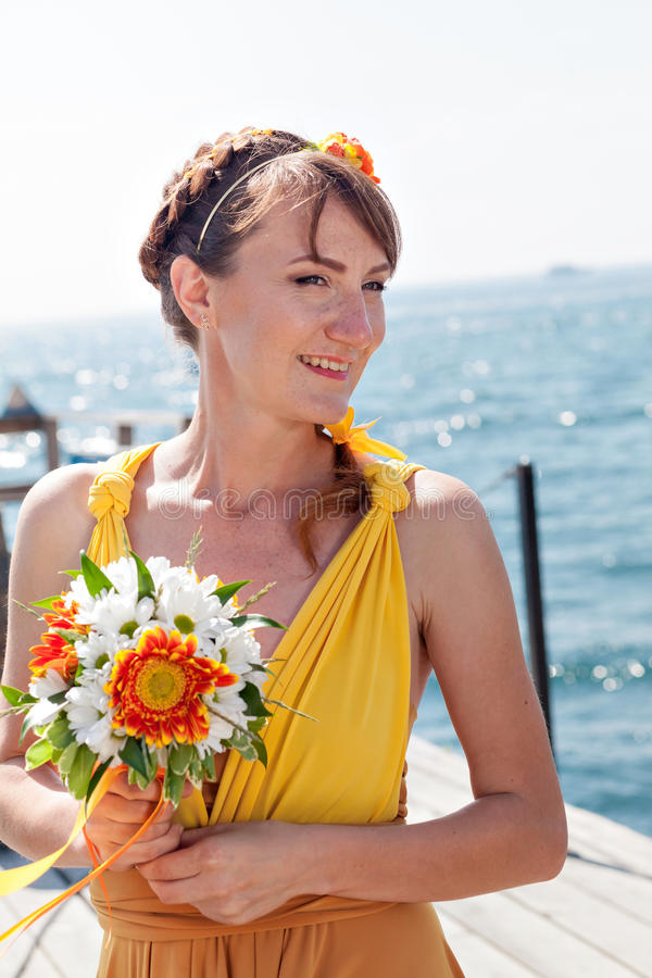 Muchacha hermosa joven en la novia anaranjada brillante en un fondo del lago Ramo del verano en las manos fotografía de archivo libre de regalías