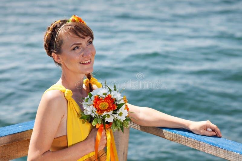 Muchacha hermosa joven en la novia anaranjada brillante en un fondo del lago Ramo del verano en las manos imagen de archivo