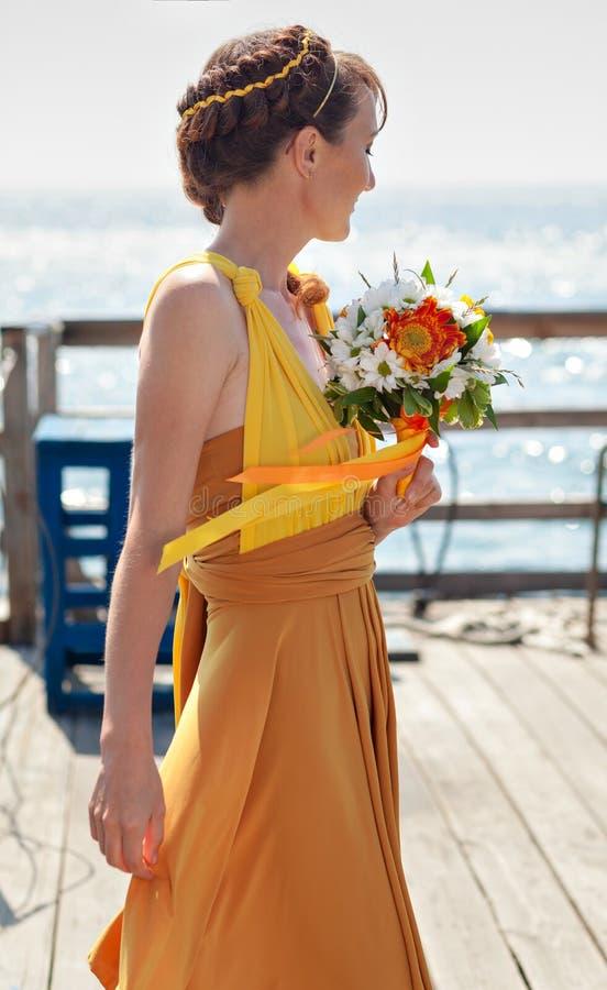 Muchacha hermosa joven en la novia anaranjada brillante en un fondo del lago Ramo del verano en las manos foto de archivo libre de regalías