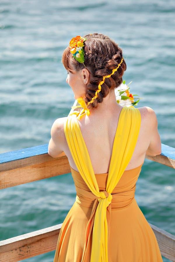 Muchacha hermosa joven en la novia anaranjada brillante en un fondo del lago Ramo del verano en las manos imagen de archivo libre de regalías