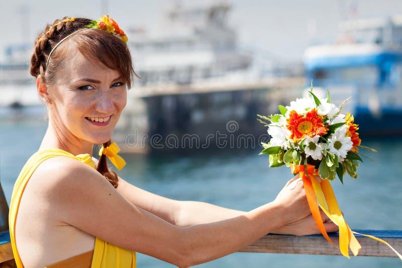 Muchacha hermosa joven en la novia anaranjada brillante en un fondo del lago Ramo del verano en las manos imagenes de archivo
