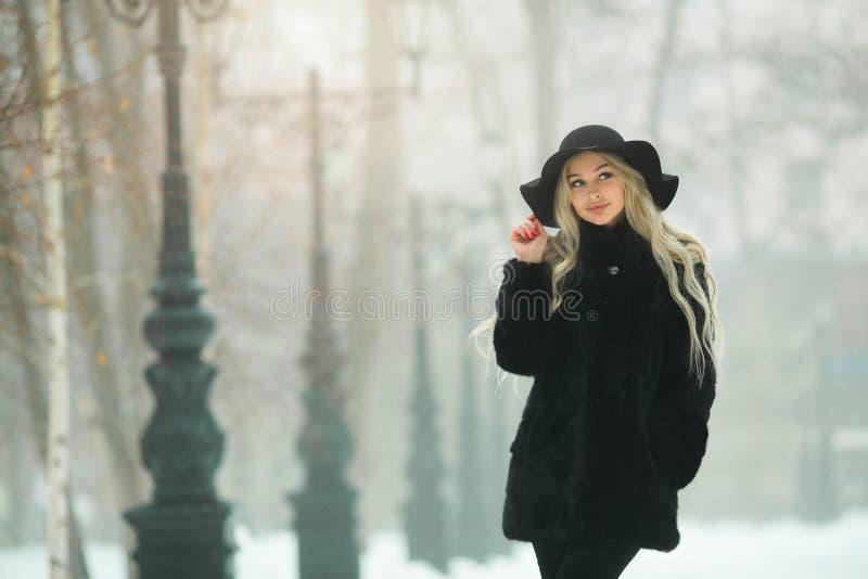 Muchacha hermosa joven en un abrigo de pieles negro imagenes de archivo